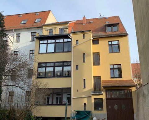 Gebäuderückseite mit Balkon und Garten